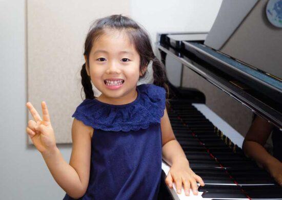 ピアノの前でピースする女の子の写真