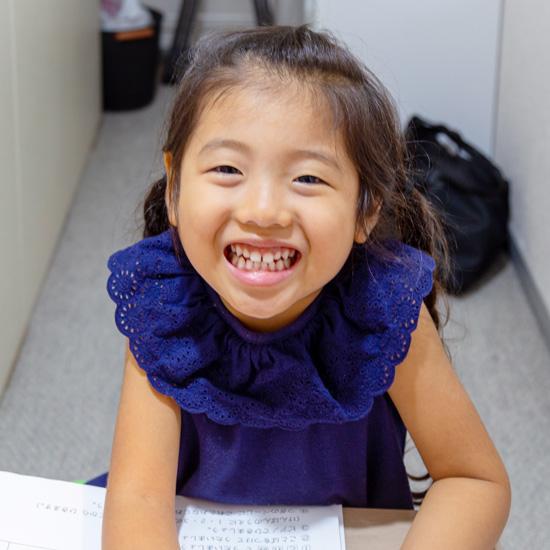 紺のワンピースを着た女の子の笑顔の写真
